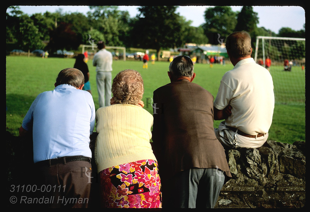 Woman and three men watch soccer match in village greens, one of few in Ireland; town of Blarney. Ireland