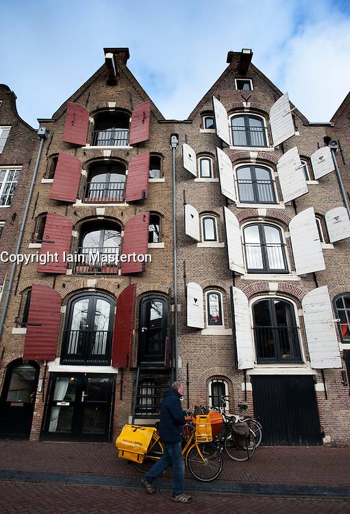 Traditional dutch houses with shutters beside canal in Amsterdam in Netherlands