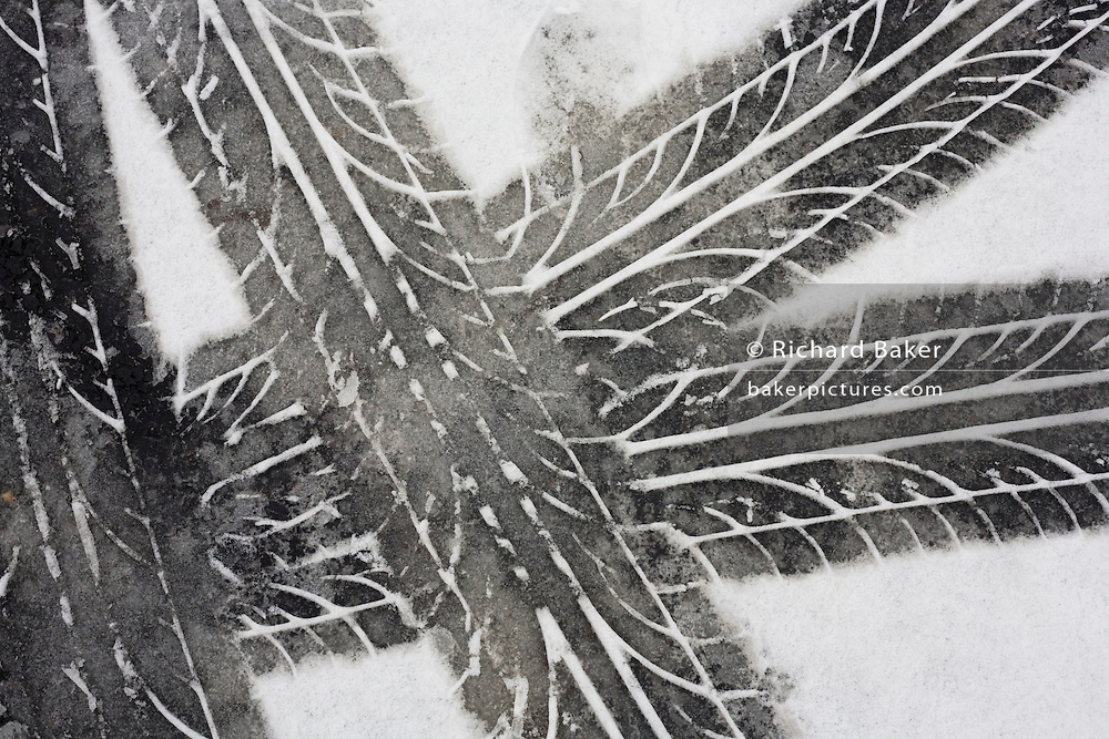 Tyre (tire) tread tracks are left as abstract patterns in melting snow after bad weather on London roads.