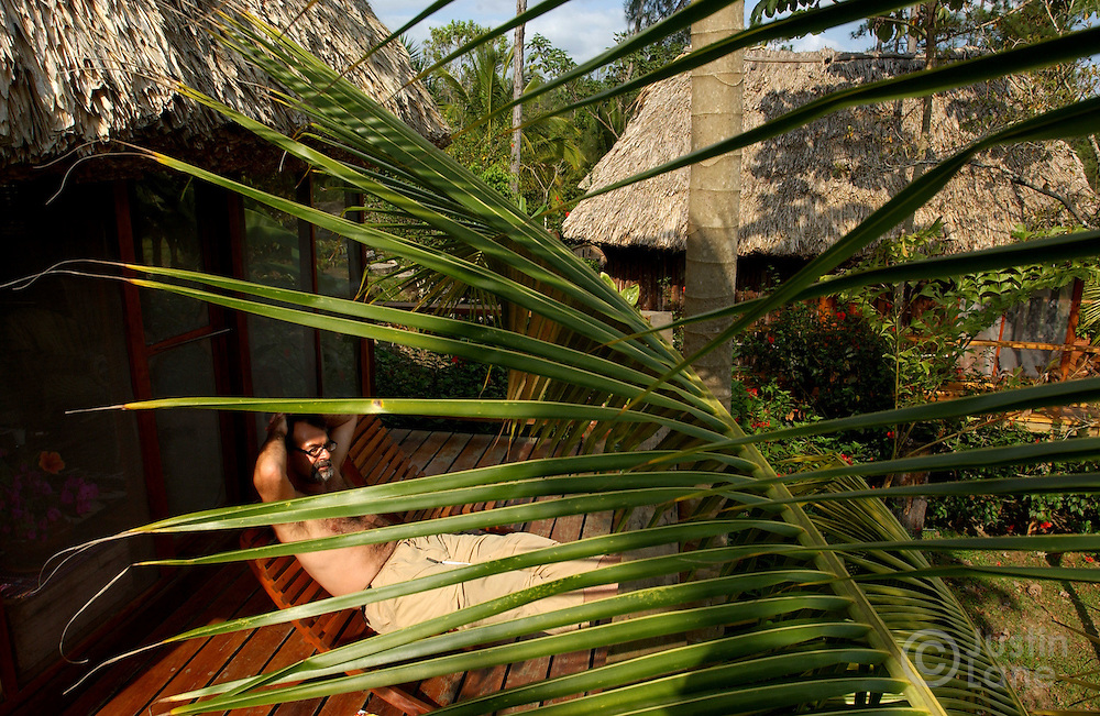 Jim C. relaxes on his porch at the Blancaneaux Lodge, one of Francis Ford Coppola's resorts, in the eastern part of Belize.<br />
