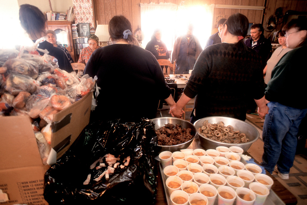 Barrow, Alaska, members of the community enjoy a traditional feast of muktuk and whale meat at the captain's house after a successful bowhead whale hunt