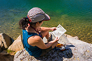 Hiker reading map on the shore of Big Pine Lake #5, John Muir Wilderness, Sierra Nevada Mountains, California USA