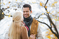 Young man looking at woman in park during autumn