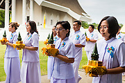 19 JULY 2014 - KHLONG LUANG, PATHUM THANI, THAILAND: Lay people participate in a procession around the ordination hall at Wat Phra Dhammakaya during an ordination ceremony. Seventy-seven men from 18 countries were ordained as Buddhist monks and novices at Wat Phra Dhammakaya, a Buddhist temple  north of Bangkok, Saturday. It is the center of the Dhammakaya Movement, a Buddhist sect founded in the 1970s and led by Phra Dhammachayo (Phrathepyanmahamuni). It is the largest temple in Thailand. The Dhammakaya sect has an active outreach program that attracts visitors from around the world.    PHOTO BY JACK KURTZ