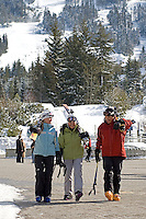 Three skiers walk through Whistler Village on a sunny winter day, Blackcomb Mountain in the background.