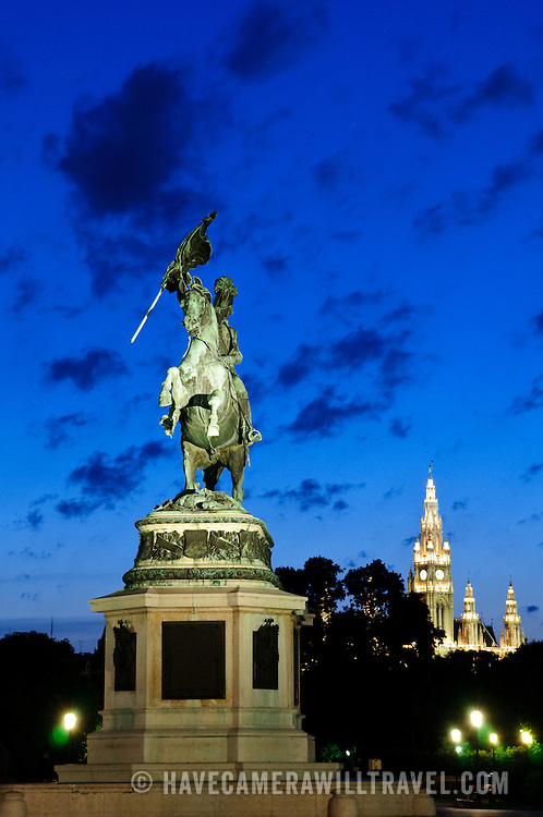 Statue in the courtyard of the Hofburg (Court Palace), Vienna, with the Rathaus illuminated in the background
