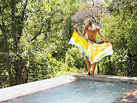 Young woman standing by swimming pool holding wraparound skirt back view