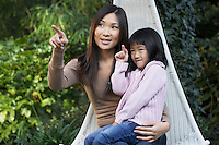 Mother sitting with daughter on lap outside pointing