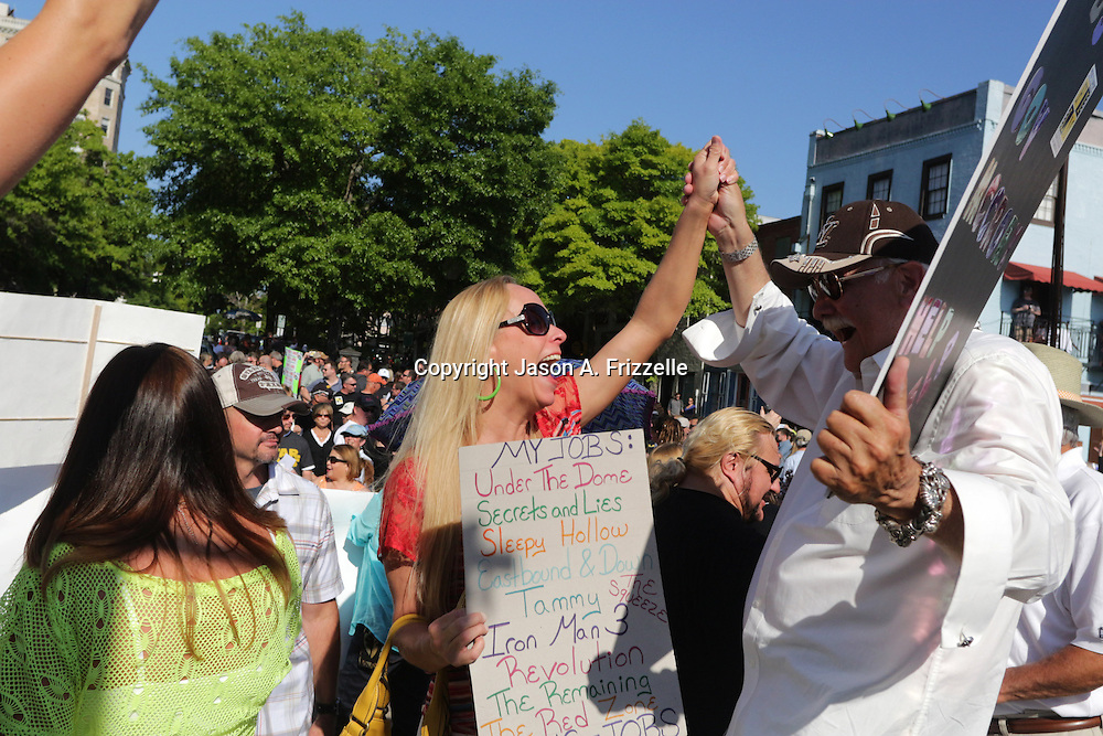 Michele Bone, left and David Poppe dance during a pro film incentives rally Sunday May 4, 2014 in Wilmington, N.C. (Jason A. Frizzelle)
