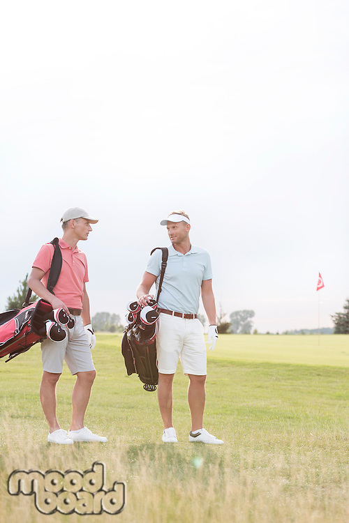Full-length of men conversing at golf course against clear sky