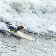 Female surfer is surfing in waves in Port Aransas, Texas.