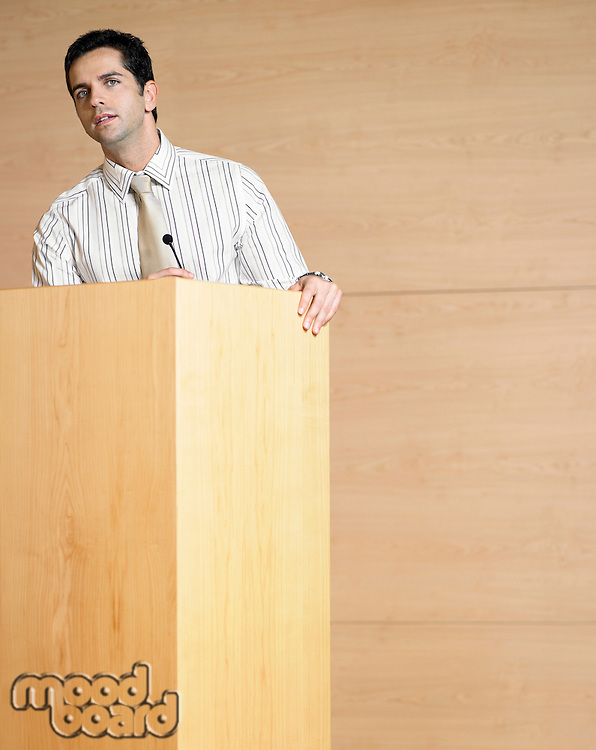 Businessman talking at podium in conference room