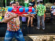 "13 APRIL 2018 - BANGKOK, THAILAND:  A tourist with a ""super squirter"" type water gun on Silom Road during the first day of Songkran in Bangkok. Songkran is the traditional Thai New Year celebration best known for water fights.     PHOTO BY JACK KURTZ"