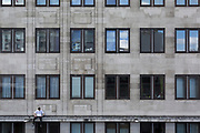 A young man sits on an exterior ledge, benneath apartments at Waterloo, on 5th March 2019, in London, England.