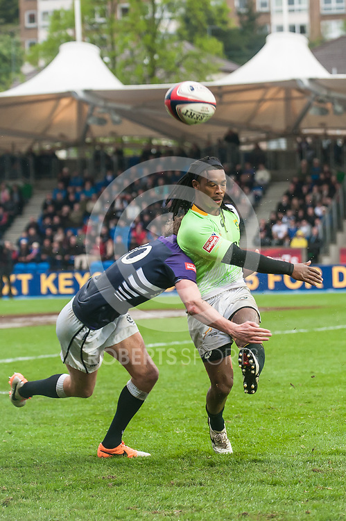 South Africa's Justin Geduld kicks into touch as he's tackled by Scotland's Scott Wight. Action from the IRB Emirates Airline Glasgow 7s at Scotstoun in Glasgow. 4 May 2014. (c) Paul J Roberts / Sportpix.org.uk