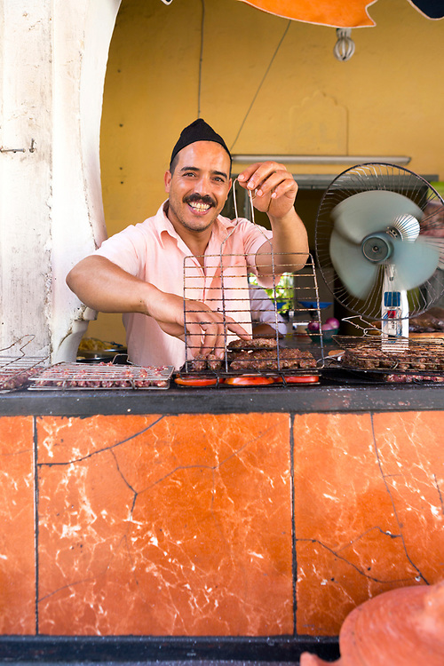 Beef Kefta street food, Moulay Idriss, Middle Atlas, Morocco 2016-08-11.<br /><br />Kefta refers to all things minced in Moroccan Darija and street food beef kefta is generally small patties of beef which have been spiced with cumin, paprika, garlic, onions and parsley and cooked over hot charcoals to add a smokey flavour. It can be served up as a sandwich which is stuffed with griddled onions and and tomato but can also come as as a platter with plates of olives, harissa paste, griddled tomatoes, onions and crusty bread. <br /><br />Lying in the heart of Morocco's most treasured agricultural region, with fertile ground for livestock, Moulay Idriss is famous for it's beef kefta speciality. <br /><br />Like many Moroccan dishes, the key is adding final touches at the end suited to your own taste. Sprinkle with heavy pinches of freshly ground cumin, salt, black pepper and paprika to really understand why it's so popular. <br /><br />The patties can also be prepared as a tagine by covering them in tomato sauce and slow cooking. Eggs are often cracked into the middle of the sauce with a sprinkle of fresh parsley during the final stages of cooking.<br /><br />Whether served up as a sandwich with charcoal griddled onions and tomato, eaten as platter with plates of olives, harissa paste, griddled tomatoes and onions or slow cooked in a tagine by covering them in a spiced tomato sauce and cracking eggs in at the end, kefta is a favourite street food in Northern Morocco.