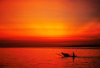 A deep red sunset view of an islander paddling his outrigger canoe alone across an endless waterscape paints a conceptual; picture of humanity's fate in the face of climate change. Conservation photography by Djuna Ivereigh.