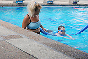 Female swimming instructor teaches a boy of eight to swim