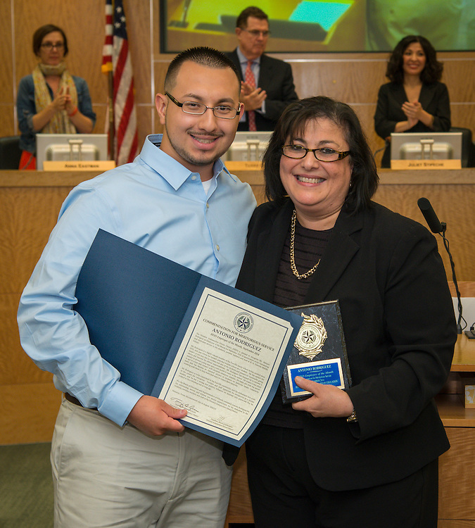 Antonio Rodriguez, left, is recognized by Fonville Middle School principal Iris Reyes, right, as the September district employee of the month during the Houston ISD Board of Education meeting, August 14, 2014.