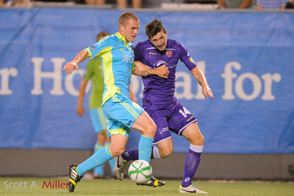 Seattle Sounders forward Will Bates (28) and Orlando City Lions midfielder Luke Boden (14)  go for a ball during a USL Pro soccer gameat the Citrus Bowl on Aug. 11, 2013 in Orlando, Florida. <br /> <br /> &copy;2013 Scott A. Miller