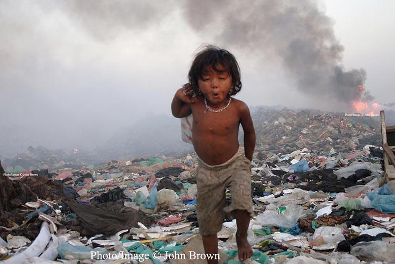 One of the youngest workers at The Stung Meanchey Landfill in Phnom Penh, Cambodia, walks across a field of garbage breathing heavily polluted air.