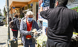 Volunteers distribute daily meal cooked at the premises of the social kitchen 'The other human' to homeless people in central Athens on 15 April 2020. - The social kitchen appeared in the middle of the Greek financial crisis, adapting now during the COVID-19 pandemic and confinement, distributing meals to unemployed, migrants, homeless and elderly people.<br />