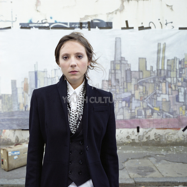 Young woman standing on street with painting of a cityscape behind her and suitcase on pavement.