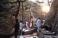= Gut Shamanist ceremony in Chirisan Mountains  Seoul  Korea   ///  Gut ( cérémonie chamaniste) dans la montagne de Chirisan , une jeune femme malade essaie de se libérer avec l'aide d'un chaman et de ses aides  Namwon  coree Le chaman, reconnaissable à sa coiffe de tulle blanc, psalmodie devant l'autel au pied de la falaise tandis que sa cliente vêtue de soieries aux couleurs de l'arc-en-ciel (saekdong) prie sous le contrôle d'une assistante vêtue de blanc. +