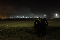 October 24, 2016 - Calais, France - Police officers secure in the Calais Jungle during small clashes a brownfield in Calais, France on 24 October 2016. The refugee camp on the coast to the English Channel is to be cleared today. The approximately 8,000 refugees are distributed after the registration by busses to various reception centers in France. (Credit Image: © Markus Heine/NurPhoto via ZUMA Press)