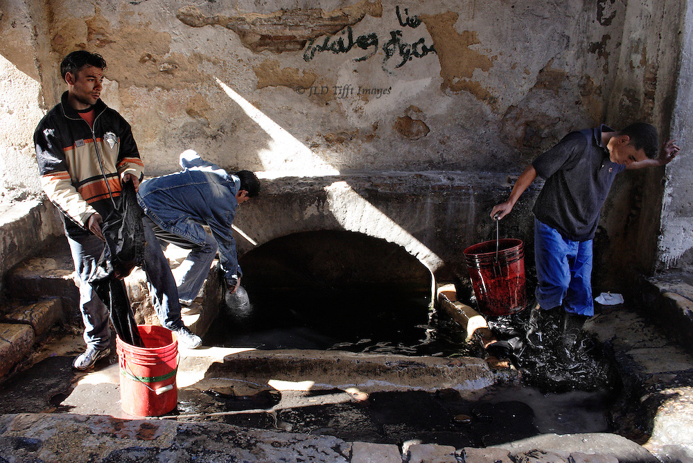 Three young men working at rinsing out freshly dyed clothing at a water source in the medina of Fes.  Onelifts a pair of jeans out of a bucket; another dips a jug into the water; a third carries a bucket while trampling on some rinsed clothes to wring them out.