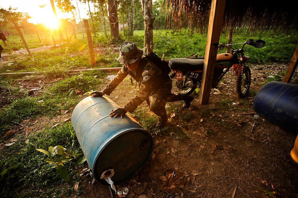 "A Bolivian FELCN Special Forces agent confiscates a barrel of gasoline, used to make cocaine-base, during a raid in Villa Nuevo Horizonte, a dangerous area in the department of Santa Cruz were narcotraffiking runs rampant. FELCN officials report it is the area of Bolivia most thickly dense of narcotraffickers and cocaine-base processing laboratories.  FELCN police commonly referred to it as a ""narco pueblo""."