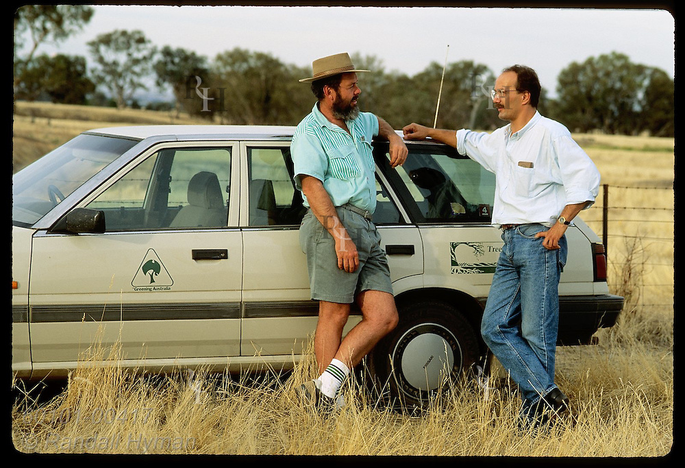 Greening Australia regionl rep, Dick Green, talks reforestation with man in farm field; NSW. Australia