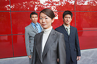 Businesspeople Standing outside beside red building