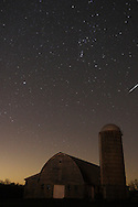 Otisville, New York - A meteor flashes through the night sky, at far right above silo, over a barn during the Orionid meteor shower on Oct. 21, 2012. The constellation Orion, with the three stars in his belt pointing to the upper right, is to the upper left of the meteor.