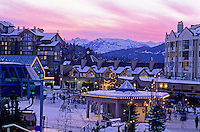 Whistler Village skier's plaza is lit by a pink sunset in winter.
