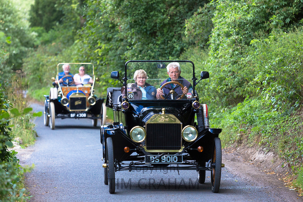 Well-preserved veteran Model T Ford autos touring along country lane in The Cotswolds, UK