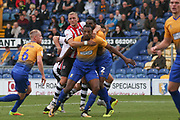 Dean Moxey of Exeter City (21) holding Krystian Pearce of Mansfield Town (5) and Hayden White of Mansfield Town (2) during the EFL Sky Bet League 2 match between Mansfield Town and Exeter City at the One Call Stadium, Mansfield, England on 15 September 2018.