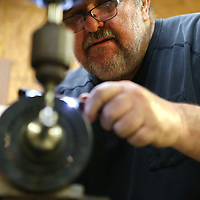 Crew keeps an eye on the turning lathe as he dials in the correct setting while making the muzzle brake.