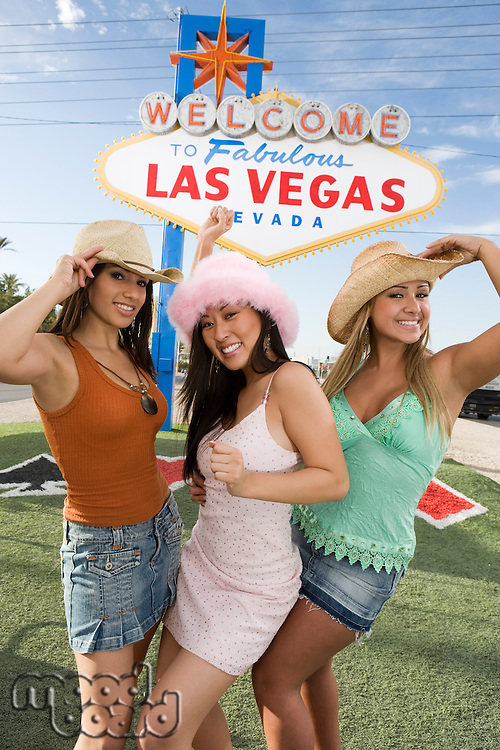 Women posing in front of Las Vegas welcome sign, Nevada, USA
