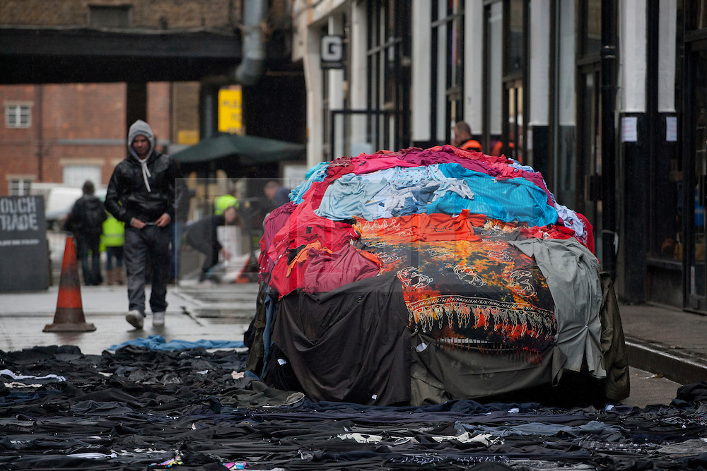 © licensed to London News Pictures. London, UK 26/04/2012. A car covered with clothes in a street covered with clothes from walls, the road, and the pavement to a fabric-strewn bench, car and even a dog to illustrate future uses for old clothes in Brick Lane. M&S will be accepting people's old and unwanted clothes for their charity campaign with Oxfam. Photo credit: Tolga Akmen/LNP