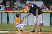 Erial's Carl Foltz  gets helped up by his first base coach after tripping over first base during a Section 4 Little League final against Cherry Hill held in Gloucester Sunday night.