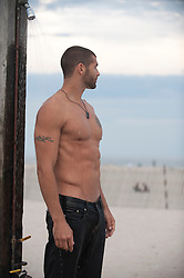 good looking shirtless man standing in an outdoor shower at the beach
