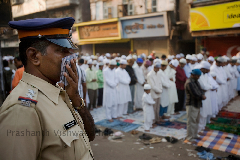 A policeman stands guard as Muslims pray to mark Eid al-Adha on a street in Mumbai December 9, 2008. Muslims around the world celebrate Eid-al-Adha, marking the end of the haj, by slaughtering sheep, goats, cows and camels to commemorate Prophet Abraham's willingness to sacrifice his son Ismail on God's command. Leading Islamic seminary Dar-ul-Uloom has suggested to Muslims in the country that they avoid slaughtering cows on Eid-ul-Azha as a mark of respect to the religious beliefs of Hindus..