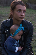 Young Roma woman with her daughter during the wake for a deceased relative in the village of Valea Seaca in Bacau County, Romania.