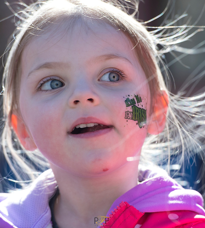 3 year old Ella Heisler of Fond du Lac, wonders at the St. Patrick's Day parade going down Main Street in Fond du Lac. March 17, 2018, Patrick Flood Photography