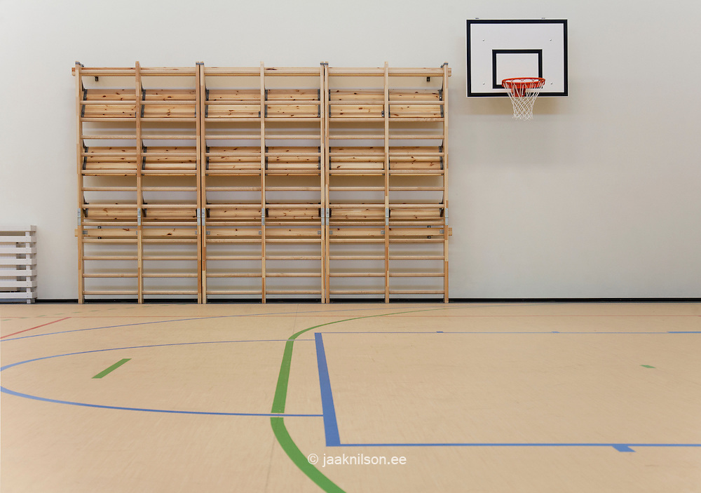 Indoor gym, marked basketball court with hoop and  backboard. Climbing equipment along wall. Village school in Metsapoole, Estonia.