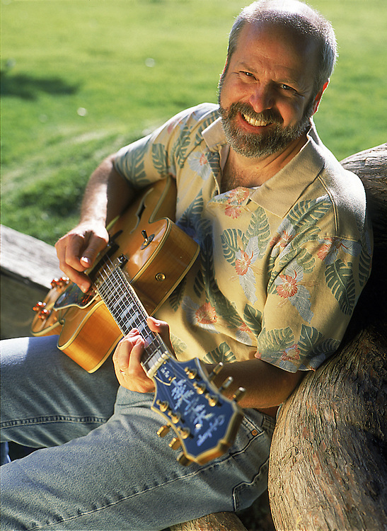 Man playing guitar and smiling at park in Del Mar, California, USA, North America.  Portrait Photographer, Robert Randall