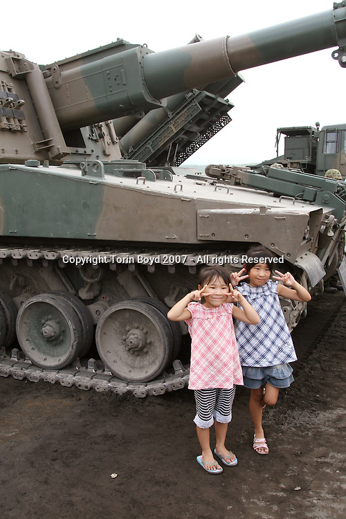 """Sisters Yuka Endo, age 5 (red top left) and Ayano Endo, age 7 (blue top right) of Saitama Prefecture flash peace signs for their parent's camera while posing in front of a Type 75 Self-Propelled 155 MM howitzer, also called the 75HSP Longnose in Japan. This took place immediately after the Japan Ground Self Defense Force's annual live fire exercise at the Higashi Fuji training range in Gotemba, Shizuoka Prefecture. Officially entitled """"Fire Power 2007 in Fuji"""", this sold-out public event held on August 26, 2007 at the base of a cloud obscured Mt. Fuji involved about 2000 military personnel, 60 tanks and armored vehicles and 20 aircraft. Japan spends nearly $40 billion annually on it's defense budget and its growing strength is the topic of much debate. This is due to Japan's political power brokers who want to rearm Japan by revising Article 9 of the constitution, thus changing the pacifist policy of the country. This is of much concern to Japan's Asian neighbors, but is also encouraged by the US government."""