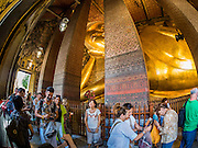 11 AUGUST 2016 - BANGKOK, THAILAND: Tourists walk past the famous reclining Buddha statue at Wat Pho. Wat Pho (the Temple of the Reclining Buddha), is formally known as Wat Phra Chetuphon. It's one of the largest temple complexes in Bangkok and best known for the giant reclining Buddha that measures 46 metres long and is covered in gold leaf. There is also a large ordination hall and the best known massage school in Thailand on the temple grounds.        PHOTO BY JACK KURTZ