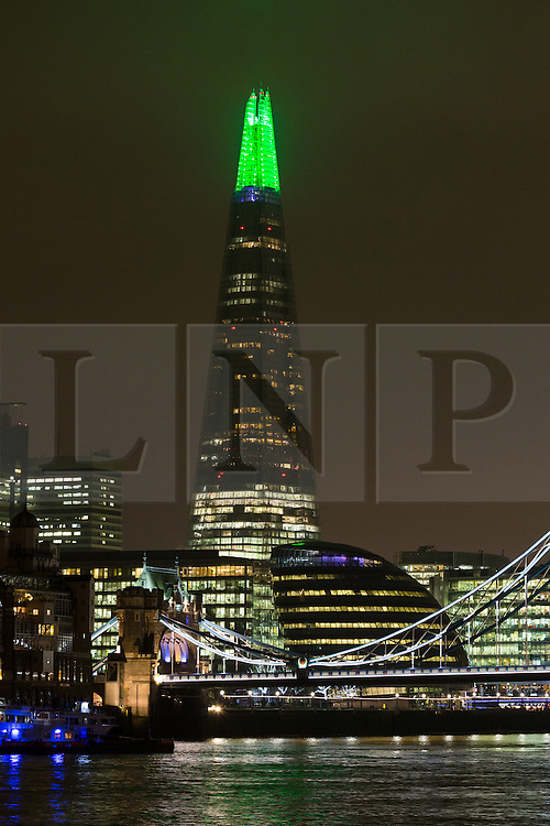 © Licensed to London News Pictures. 14/12/2015. London, UK.  The London Shard is lit up in alternating festive red, green and white colours during the run up to Christmas. Photo credit : Vickie Flores/LNP